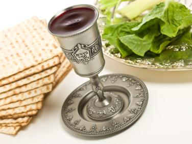 A kiddush cup, Seder plate and matzo for Passover. Words from the traditional Hebrew blessing of the wine are written on the cup.