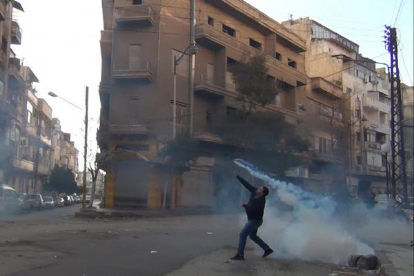 The Syrian uprising began a year ago. Here, a protester in Homs throws a tear gas canister back at security forces on Dec. 27, 2011.