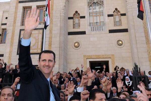 President Assad waves to supporters after a speech at the parliament in Damascus on March 30.