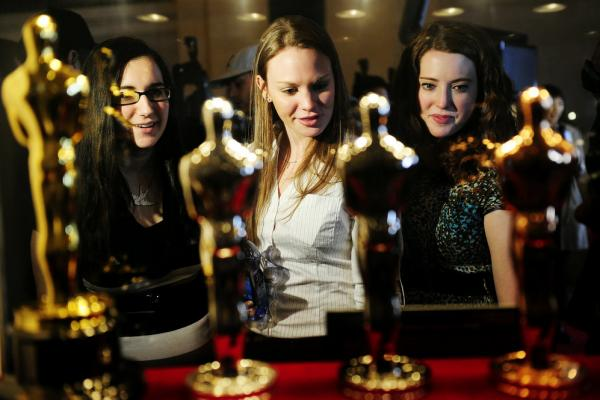 "Oscar fans in New York take a closer look at the statuettes on display during the ""Meet the Oscars, Grand Central"" exhibition at Grand Central Station on Feb. 22."