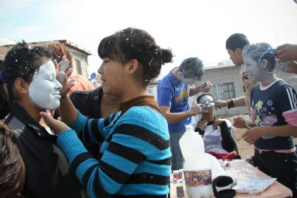 In the Tierra Nueva neighborhood of Ciudad Juarez, youth church members get ready for their weekly outing as messenger angels by painting and applying glitter to their faces. Their wings are made with goose down, and their robes are old curtains.