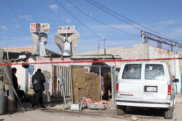 Messenger angels hold signs on a rooftop near a recent murder site. Police and investigators are on the scene, although murders are rarely solved in Ciudad Juarez.