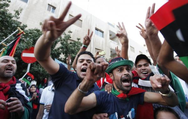 Libyans celebrate Moammar Gadhafi's death in front of the Libyan Embassy in Amman, Jordan, on Thursday.