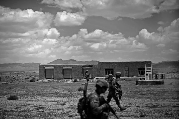 Soldiers walk past an abandoned gas station after a gun battle with insurgents near the village of Pana, Ghazni province.