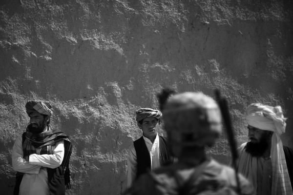 A soldier stands in front of a group of men from Babaker, while they wait to be questioned by Afghan National Army troops.