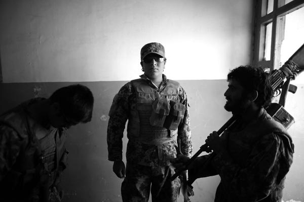 Zafar, an Afghan army soldier, waits in the doorway of what was once an elementary school for the village of Pana, but now serves as the soldiers' barracks and headquarters.