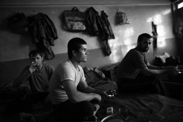 Abdul Khalik (center), from Badakhshan province in northern Afghanistan, shares a cup of tea with fellow Afghan army soldiers after Friday prayers in an old school building that they call home.