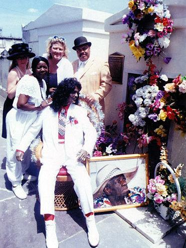 Antoinette K-Doe (second from the left) stands with friends around a statue of her deceased husband, Ernie, at the St. Louis No. 2 tomb. Antoinette is buried in the tomb, and her mother — Ernie K-Doe's second and favorite mother-in-law, Leola Clark — is shown in the portrait. Clark is buried in the tomb, too.