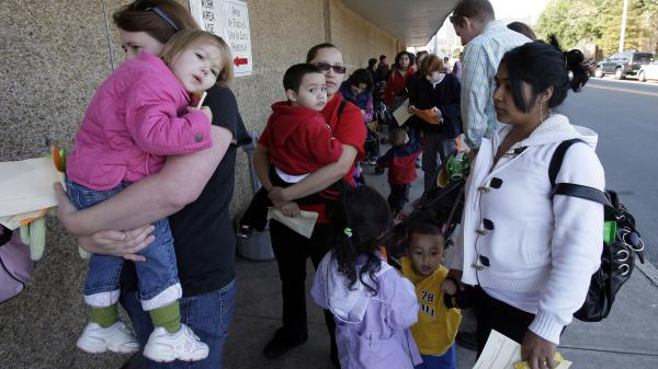 People wait in line at the Durham County Health Department for the H1N1 flu vaccination in Durham, N.C., in November 2009.