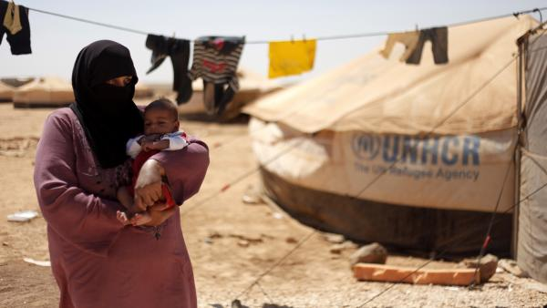 Omm Ahmed, a refugee from Daraa, Syria, carries her infant near her tent at Zaatari Refugee Camp in Mafraq, Jordan, on Sunday. Syrian civilians have borne the greatest brunt of the conflict in their country.
