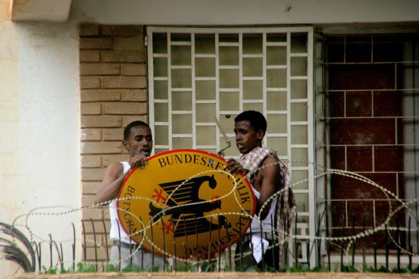 Sudanese demonstrators remove the German embassy sign after storming its premises in Khartoum.
