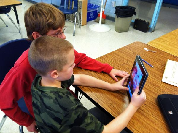 In Durham, N.H., Oyster River Middle School seventh-graders Patrick Beary and Morgan Bernier play with StoryKit, a free app that helps middle-schoolers put together simple presentations, and elementary students make storybooks.