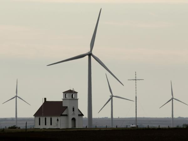 Wind turbines dwarf a church near Wilson, Kan. The White House wants to extend a federal wind energy credit, but the Romney campaign wants to let it expire.