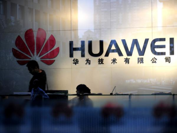 "Staff and visitors walk past the lobby at the Huawei office in Wuhan, China. Beijing has urged Washington to ""set aside prejudices"" after a draft congressional report said Chinese telecom firms Huawei and ZTE were security threats that should be banned from business in the U.S."