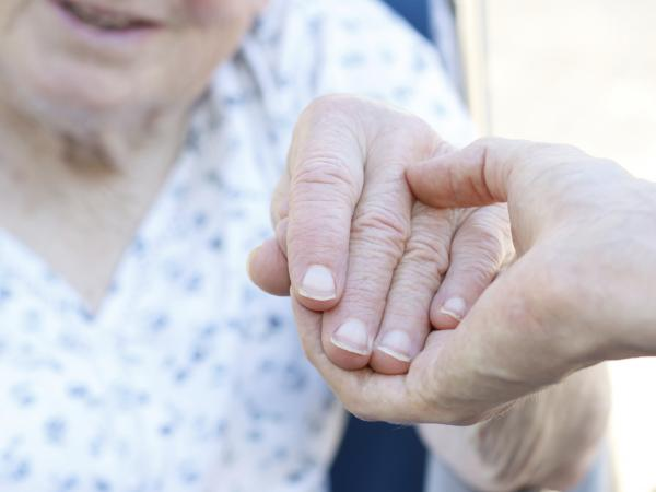 Senior woman in wheelchair holding hands with caretaker