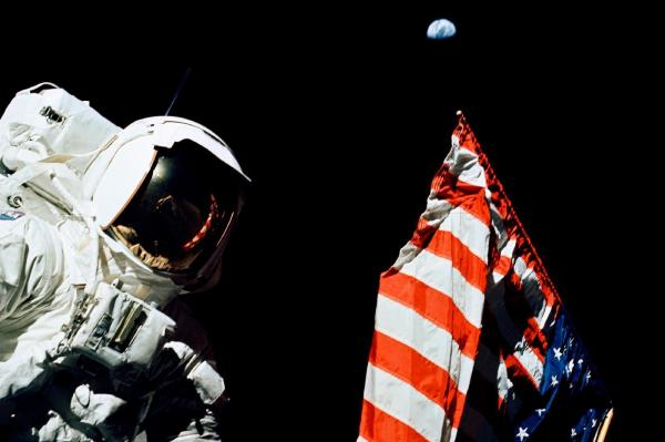 Schmitt stands by the American flag during a moonwalk. Look above the flag — that's Earth, a quarter-million miles away.