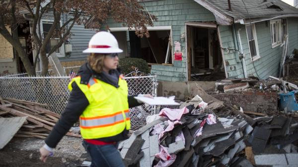 A woman with the Army Corps of Engineers documents a destroyed home last month in a residential area of New Dorp Beach on Staten Island in New York City.