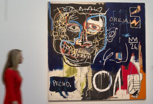 "A Sotheby's employee walks past a work by Jean-Michel Basquiat titled ""Untitled (Pecho/Oreja)"" at the auction house."