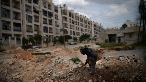 A Syrian rebel patrols the area in the Sheikh Maqsud district of the northern city of Aleppo, on Thursday.