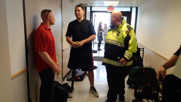 Marine Sgt. Maj. Damion Jacobs (left) and Marine Capt. Cam West visit with Boston emergency workers who responded to the bombings at the Boston Marathon.