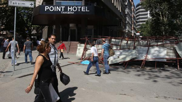 Pedestrians pass a barricade outside a hotel at Taksim Square, Istanbul. Business people say they are nervous that protests are cutting deep into tourism.