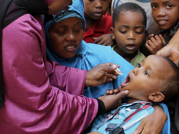 Health workers vaccinate a boy against polio at a May immunization drive in Mogadishu, Somalia.