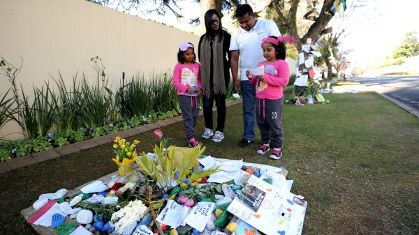 A family brings a message of good wishes for former South African President Nelson Mandela outside his house in Johannesburg Monday. Mandela, 94, is in critical but stable condition.