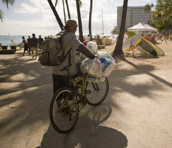 A homeless man collects cans on Waikiki Beach in 2010 in Honolulu. Under a new pilot program, some homeless people will get help from the state to reunite with relatives on the mainland.