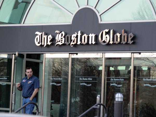 A man walks out of <em>The Boston Globe</em> headquarters on Feb. 20, the day The New York Times Co. said it planned to sell the paper.