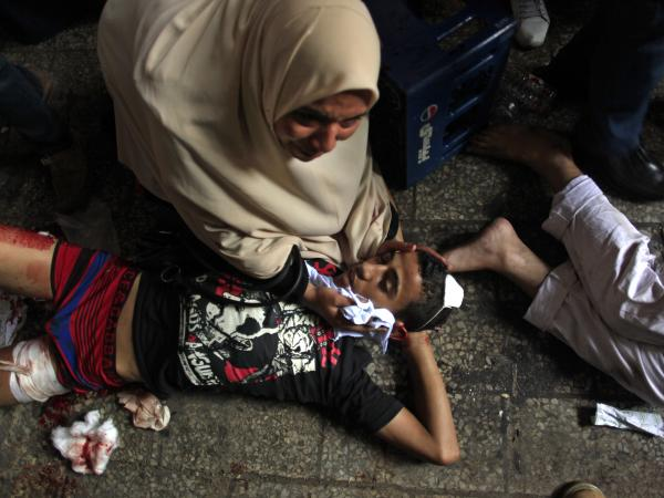 Egyptians lie on the ground after being injured during clashes between security forces and Morsi supporters in Ramses Square in Cairo on Friday.
