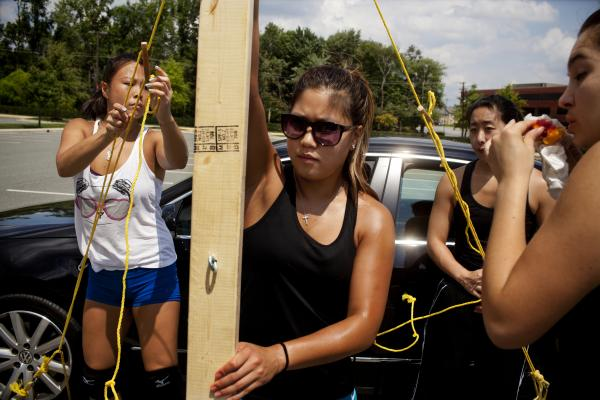 "Stephanie Moy, 23, (center) sets up a volleyball net with her teammates at a practice in Rockville, Md. Women's teams also compete in the North American Chinese Invitational Volleyball Tournament. ""CYC is a family thing,"" she says, ""Our fathers played together. It's like tradition. I want my kids to play for CYC."""
