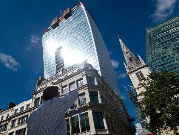 "A man reacts to a shaft of intense sunlight reflected from the glass windows of the new ""Walkie Talkie"" tower in central London on Aug. 30."