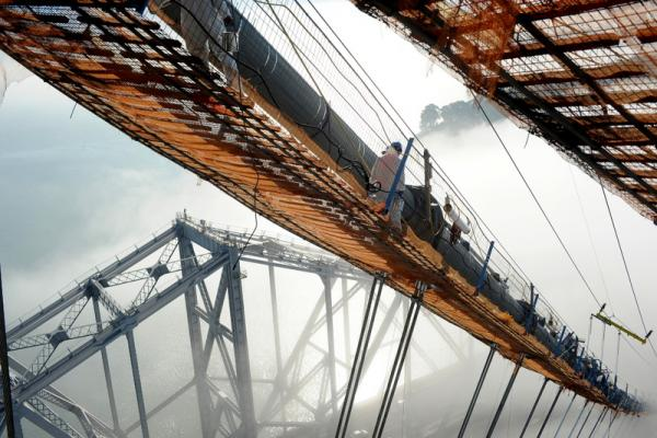 Laborers carrying cans of Grikote anti-corrosion paste on the south-side span catwalk in the fog, 2012. (Copyright © Joseph A. Blum)
