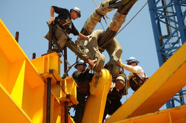 Ironworkers C.J. Biskner, Matt Cochran and Jerry Kubala connecting 600-ton shackles and heavy rigging to OBG deck lifting frame lug, 2010. (Copyright © Joseph A. Blum)