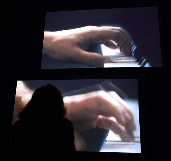 A visitor takes in Anri Sala's <em>Ravel Ravel Unravel</em> installation in the French pavilion of the 55th Venice Biennale.