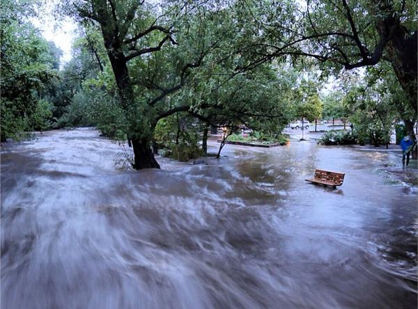 In this image made with a slow shutter speed which blurred the rushing water, flood waters course through a small park in Boulder, Colo., on Thursday.