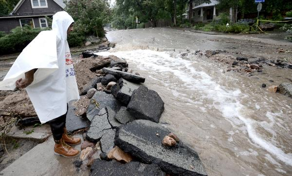 John Hoffenberg watches as floodwaters flow down a street in Boulder, Colo., on Sunday.