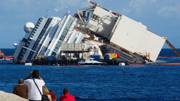 The view Monday from shore as work began to pull the Costa Concordia upright. The box-like structure on the ship's port side is one of the refloating caissons that will stabilize the ship.