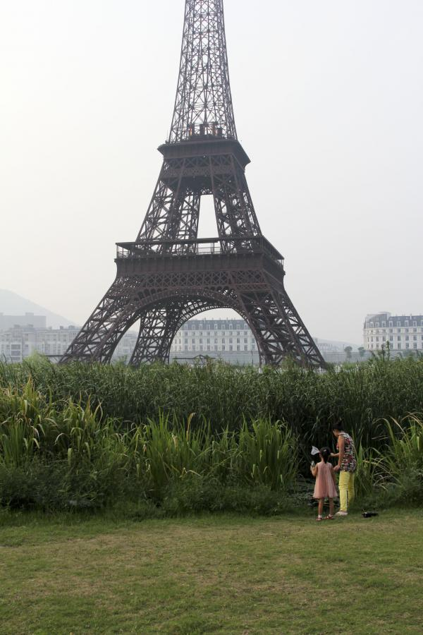 A girl and her mother catch fish in a pool of water near Sky City's signature structure: a 300-foot-plus Eiffel Tower.