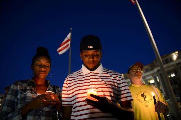 Brittany Carter (left) and Jibri Johnson of Bowie, Md., and Bryan Beard of Washington attend a candlelight vigil for the victims, at Freedom Plaza on Monday night. The vigil was organized by Project End Gun Violence.