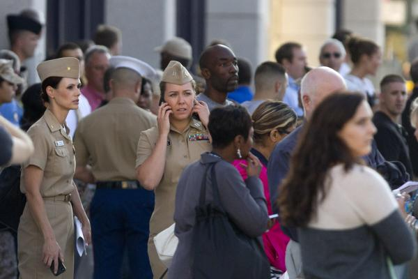 Family and friends wait to meet staff of the Naval Sea Systems Command headquarters on Monday. Employees were told to shelter in place for most of the day.