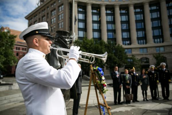 A member of the U.S. Navy plays taps during the wreath-laying ceremony.