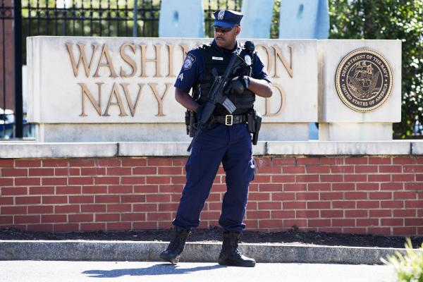 An officer from the Department of Defense stands guard near the gate at the Washington Navy Yard, which was closed to all but essential personnel on Tuesday.