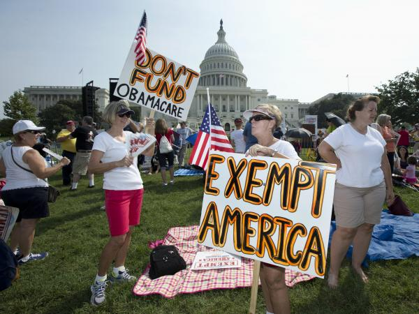 "Linda Norman (right) and Joanna Galt, both from Florida, hold their banners during a ""Exempt America from Obamacare"" rally on the West Lawn of the Capitol on Sept. 10."
