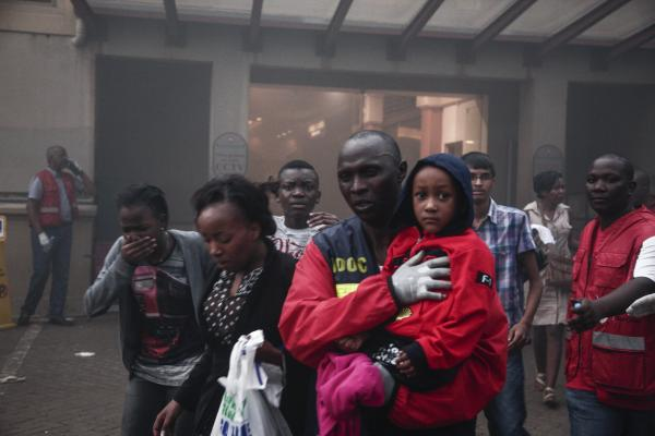 People escape from a fire allegedly started by gunmen inside the mall Saturday.