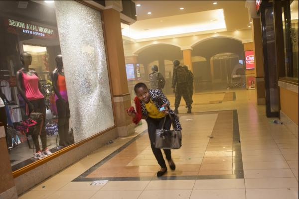 A woman who had been hiding during the gunbattle runs for cover after armed forces enter the mall.