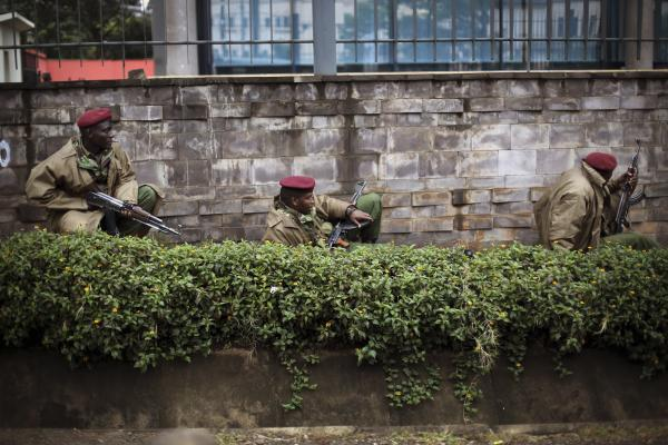 Kenya security forces monitor the scene behind a wall outside the Westgate Mall in Nairobi on Monday. Kenya's military launched a major operation at the upscale mall and said it had rescued most of the hostages being held captive by al-Qaida-linked militants during the standoff which started on Saturday.