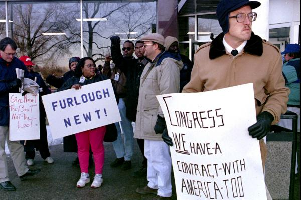 Dave Glass (right), a federal government computer assistant, and about 100 other furloughed Social Security Administration workers gather at the Arthur J. Altmeyer Building in Woodlawn, Md., on Dec. 26, to protest the temporary government shutdown.