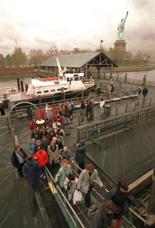 Tourists board the ferry, with the Statue of Liberty in the background, after being asked to leave Liberty Island in New York Harbor on Nov. 14.