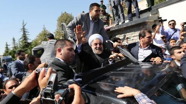 Iran's President Hassan Rouhani waves as his motorcade leaves Tehran's Mehrabad Airport upon his arrival from New York Saturday, one day after he spoke to President Obama by phone.
